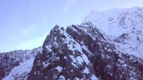 El abejón tiró lentamente estar en órbita un pico de montaña alpino escarpado y dentado en invierno almacen de metraje de vídeo