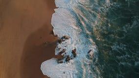 El abejón tiró volar sobre las ondas que se estrellaban en la playa en Portugal con huellas en arena almacen de metraje de vídeo