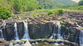 El abejón vuela de cerca de la derecha hacia la izquierda a lo largo de las cascadas