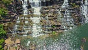 El abejón vuela de la charca a través de las cascadas espumosas entre rocas