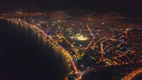 El abejón vuela sobre ciudad brillante de la noche en la playa almacen de video