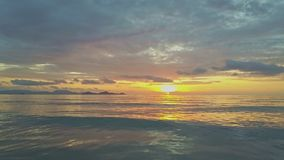 El abejón vuela sobre la resaca tranquila de la onda contra salida del sol hermosa