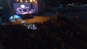 El abejón vuela sobre los anfitriones del concierto de la muchedumbre de la gente que escuchan metrajes