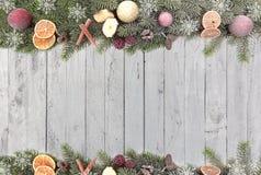 El abeto de la Navidad ramifica con las frutas de la Navidad, copos de nieve blancos como frontera contra un fondo de madera Fotografía de archivo libre de regalías