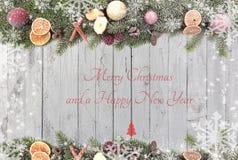 El abeto de la Navidad ramifica con las frutas de la Navidad, los copos de nieve blancos como frontera contra un fondo de madera  Imagen de archivo libre de regalías