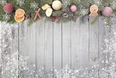 El abeto de la Navidad ramifica con los copos de nieve blancos como frontera contra un fondo de madera Fotografía de archivo libre de regalías