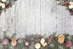 El abeto de la Navidad ramifica con los copos de nieve blancos contra un fondo de madera para la Navidad Fotos de archivo