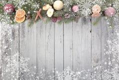 El abeto de la Navidad ramifica los copos de nieve blancos como frontera contra un fondo de madera Imágenes de archivo libres de regalías