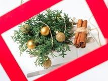 El abeto del Año Nuevo las esferas adornadas del oro de la Navidad y un paquete de leña Un marco rojo para una foto foto de archivo libre de regalías