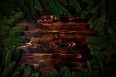 El abeto del fondo del Año Nuevo de la Navidad ramifica en marco de madera quemado Fotografía de archivo