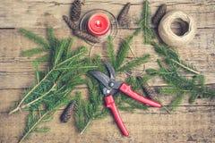 El abeto del fondo del Año Nuevo de la Navidad ramifica los conos rojos de la vela que las tijeras que cultivaban un huerto puest Imágenes de archivo libres de regalías