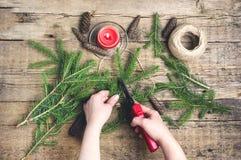 El abeto del fondo del Año Nuevo de la Navidad ramifica los conos rojos de la vela que las tijeras que cultivaban un huerto puest Fotografía de archivo libre de regalías