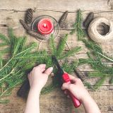 El abeto del fondo del Año Nuevo de la Navidad ramifica los conos rojos de la vela que las tijeras que cultivaban un huerto puest Imagen de archivo