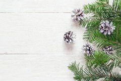 El abeto ramifica con los conos en los tableros de madera pintados un blanco cristo Imagen de archivo libre de regalías
