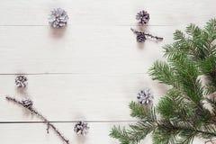 El abeto ramifica con los conos en los tableros de madera pintados un blanco cristo Foto de archivo