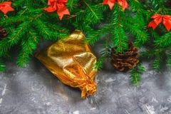 El abeto ramifica con los conos y el rojo arquea encima de un fondo concreto gris La Navidad del Año Nuevo Bolso del oro con los  Foto de archivo libre de regalías
