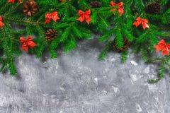 El abeto ramifica con los conos y el rojo arquea encima de un fondo concreto gris La Navidad del Año Nuevo Espacio libre para el  Imágenes de archivo libres de regalías