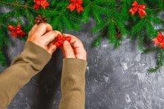 El abeto ramifica con los conos y el rojo arquea encima de un fondo concreto gris La Navidad del Año Nuevo Manos con un arco Fotografía de archivo