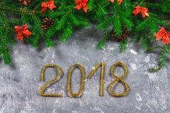 El abeto ramifica con los conos y el rojo arquea encima de un fondo concreto gris La Navidad del Año Nuevo Texto 2018 de la malla Imagen de archivo