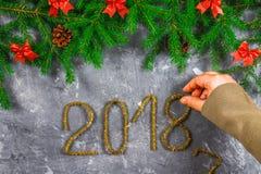 El abeto ramifica con los conos y el rojo arquea encima de un fondo concreto gris La Navidad del Año Nuevo Texto 2018 de la malla Fotografía de archivo