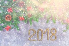 El abeto ramifica con los conos y el rojo arquea encima de un fondo concreto gris La Navidad del Año Nuevo Texto 2018 de la malla Fotos de archivo