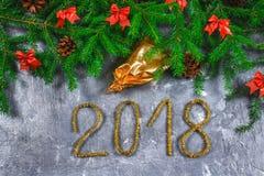 El abeto ramifica con los conos y el rojo arquea encima de un fondo concreto gris La Navidad del Año Nuevo Texto 2018 de la malla Imágenes de archivo libres de regalías
