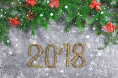 El abeto ramifica con los conos y el rojo arquea encima de un fondo concreto gris La Navidad del Año Nuevo Texto 2018 de la malla Fotografía de archivo libre de regalías