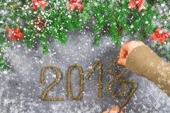 El abeto ramifica con los conos y el rojo arquea encima de un fondo concreto gris La Navidad del Año Nuevo Texto 2018 de la malla Imagenes de archivo