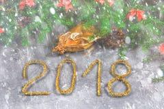El abeto ramifica con los conos y el rojo arquea encima de un fondo concreto gris La Navidad del Año Nuevo Texto 2018 de la malla Foto de archivo