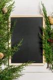 El abeto ramifica frontera y tablero de tiza negro en el fondo de madera blanco, bueno para el contexto de la Navidad foto de archivo libre de regalías