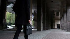 El abogado joven del hombre de negocios en traje clásico y una capa sostienen el caso con los documentos y caminan cámara lenta É almacen de video