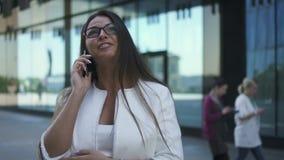 El abogado joven feliz está hablando en el teléfono que se coloca en fondo del edificio de la ciudad metrajes