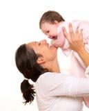El abrazo de la niña en madre arma el playingin feliz en blanco fotografía de archivo libre de regalías