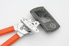 El abrelatas de poder rompe un smartphone Imagenes de archivo