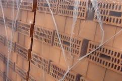 El abrigo anaranjado embaló los ladrillos listos para el emplazamiento de la obra Fotografía de archivo libre de regalías
