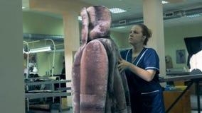 El abrigo de pieles acabado está consiguiendo examinado por una costurera metrajes