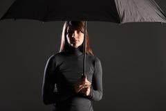 El abrigo del apuro mide el tiempo de la mujer bajo el paraguas Fotografía de archivo libre de regalías