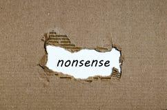 El absurdo de la palabra que aparece detrás del papel rasgado imagenes de archivo