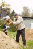 El abuelo ayuda al nieto a conseguir en una colina de la arena Foto de archivo