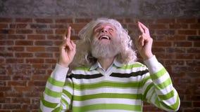 El abuelo caucásico asombroso está deseando para la suerte mostrando los fingeres cruzados y mirando que se levanta, ejemplo del  almacen de video