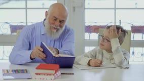 El abuelo con el nieto hace la preparación de la escuela junta almacen de video