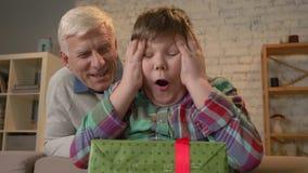 El abuelo da a su nieto un regalo Un hombre mayor da un regalo a un niño gordo Alegría, sorpresa, felicidad, emoción almacen de video