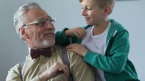 El abuelo de la cubierta del muchacho observa detrás, visita de la familia, proximidad blanda de las relaciones metrajes