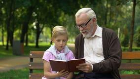 El abuelo enseña al nieto a leer el libro, anima al muchacho al conocimiento, educación almacen de metraje de vídeo