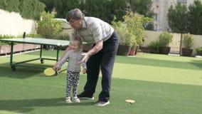 El abuelo enseña a la pequeña nieta a jugar a tenis de mesa almacen de video