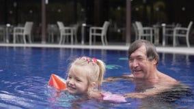 El abuelo está nadando en la piscina con su pequeña nieta almacen de video