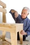 El abuelo hace una silla Fotografía de archivo