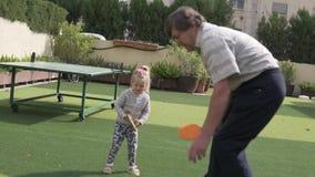 El abuelo juega a tenis de mesa con su pequeña nieta almacen de metraje de vídeo