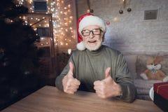 El abuelo se está sentando cerca del árbol de Cristmas en sombrero del ` s de Santa Claus en la noche en casa Imagenes de archivo