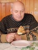 El abuelo se sentó en una tabla y come la crepe caliente con apetito foto de archivo